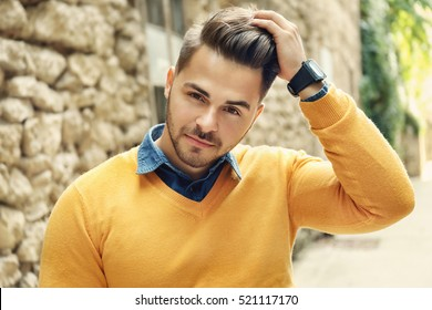 Handsome man near old building with brick wall