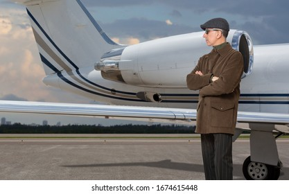 Handsome man next to a private jet at the airport.