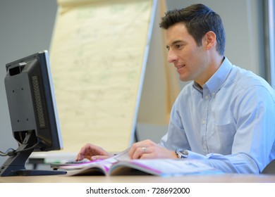 handsome man in an office with a computer at work