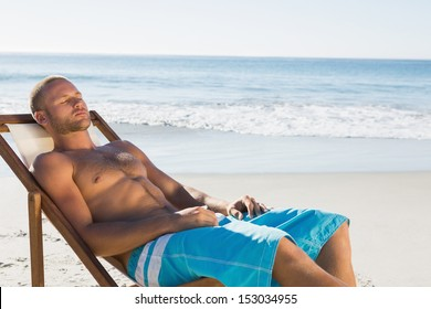 Handsome man on the beach having a nap while sunbathing on his deck chair