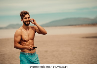 Handsome man on the beach listens to music over the earphones