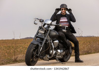 Handsome man on a black classic motorcycle