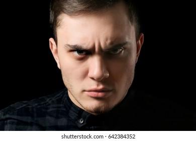 Handsome man on dark background, closeup