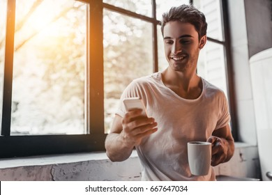 Handsome man on kitchen is smiling, drinking coffee in the morning and looking at smart phone.