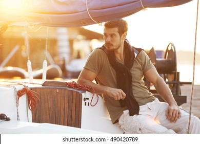 Handsome man on sailing boat in sunset.