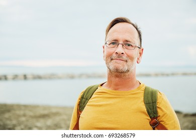 Handsome man on summer vacation by the sea, wearing yellow t-shirt and backpack