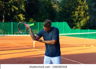 Handsome man on tennis court. Young tennis player. Pain in the elbow