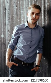 Handsome man on a wooden wall background