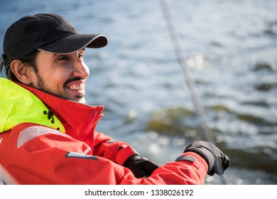 Handsome man on yacht touches white sail called assymetric spinnaker, works with tackle in sea at summer day, under view.