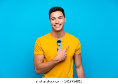 Handsome man over blue background pointing to the side to present a product