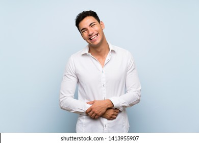 Handsome man over blue wall smiling