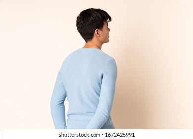 Handsome man over isolated beige background in back position and looking back