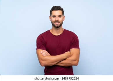Handsome man over isolated blue background keeping the arms crossed in frontal position