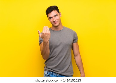 Handsome man over isolated yellow wall inviting to come with hand. Happy that you came