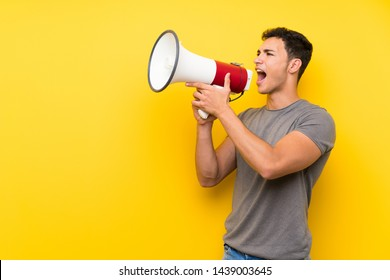 Handsome man over isolated yellow wall shouting through a megaphone
