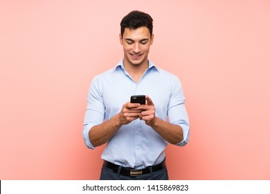Handsome man over pink background sending a message with the mobile