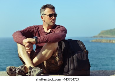 Handsome man over sea view. Outdoor male portrait. Trip, vacation, holiday, tourism, leisure, lifestyle, summer time concept.