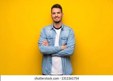 Handsome man over yellow wall keeping the arms crossed in frontal position