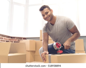 Handsome man is packing a moving box using an adhesive tape looking at camera and smiling
