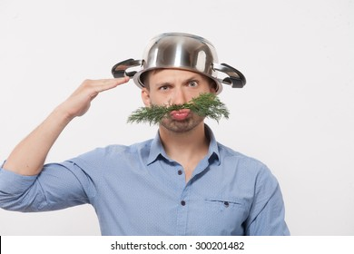 Handsome man with pan on his head and dill weed instaed of moustache. Man in blue shirt looking so funny isolated on white.