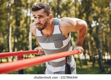 Handsome man in a park. Sportsman in a sportswear. Guy training