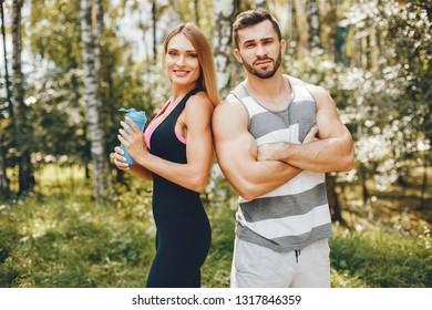 Handsome man in a park. Sportsman in a sportswear. Couple training