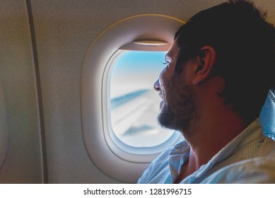 handsome man passenger traveler looking at window in airplane, travel by flight, man tourist sitting in air plane watching outside