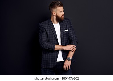 Handsome man with perfect hairdo and beard adjusting sleavs while standing against black background.