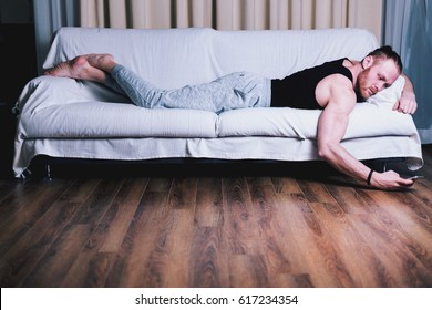 Handsome man with piercing smiling and resting on sofa holding cellphone, using smart device for chatting, shopping apps, browsing internet, checking e-mail, playing mobile games