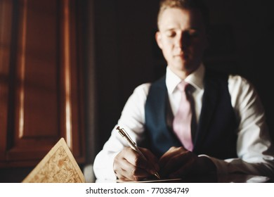 Handsome man with pink tie sits at the table and writes a letter in the dark room