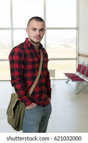 Handsome man in plaid shirt walking and posing in the hall of University.