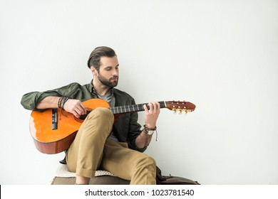 handsome man playing acoustic guitar and leaning on wall isolated on white