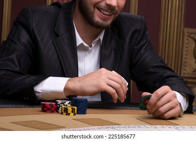 Handsome man playing  in casino smiling  holding in hands chips and cards sitting at table selective focus