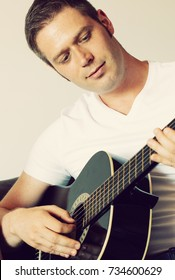 Handsome man playing guitar at home.