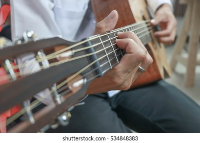Handsome man playing guitar left.close up.selective focus