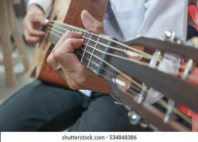 Handsome man playing guitar.close up.selective focus