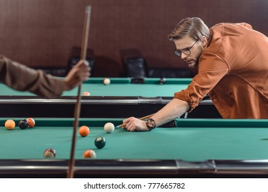 handsome man playing in pool at bar