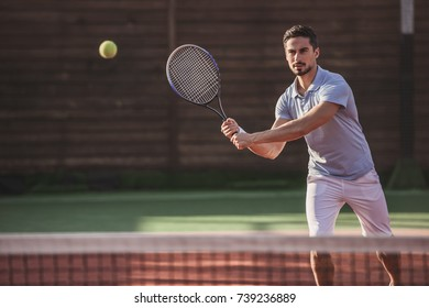 Handsome man is playing tennis on tennis court outdoors