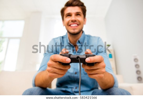 Handsome man playing video games, focus on joystick