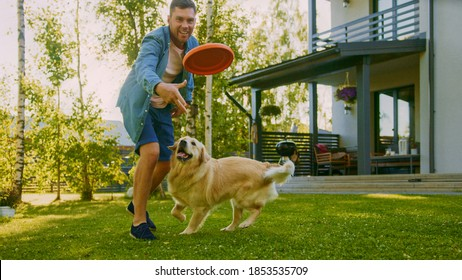 Handsome Man Plays Catch flying disc with Happy Golden Retriever Dog on the Backyard Lawn. Man Has Fun with Loyal Pedigree Dog Outdoors in Summer House Backyard. - Shutterstock ID 1853535709
