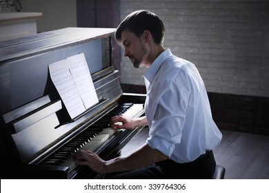 Handsome man plays piano in the class