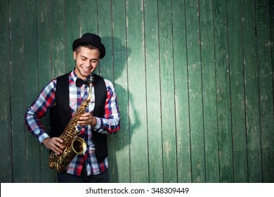 Handsome man plays saxophone on green wooden background