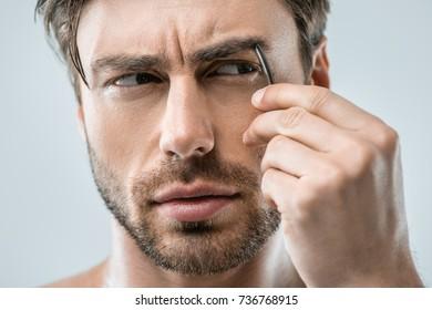 handsome man plucking eyebrows with tweezers, isolated on grey