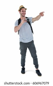 Handsome man pointing with retro camera on white background