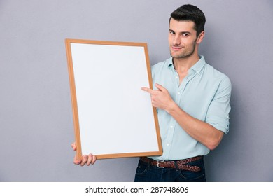 Handsome man pointing at white blank board over grey background