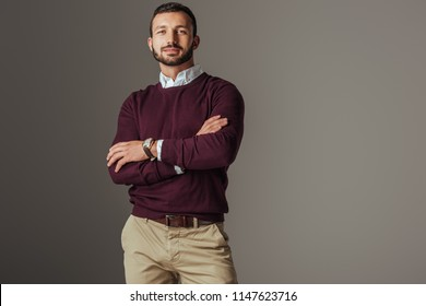 handsome man posing in burgundy autumn sweater with crossed arms, isolated on grey