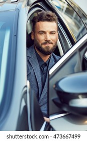 Handsome man posing in a car on driver's place