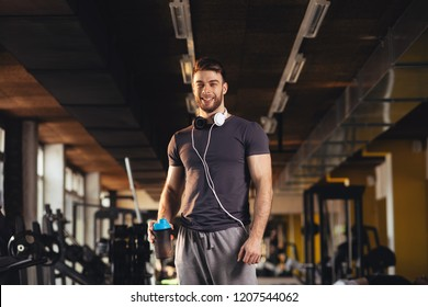Handsome man posing with shaker bottle of protein in hand after workout at the gym