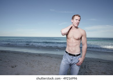 Handsome man posing shirtless by the shore
