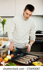 Handsome man pouring oil in raw fish on roasting pan